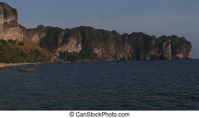 view of city beach with longtail boats and tourists -...