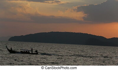 longtail boat drifts against sunset above sea - longtail...