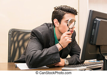 Businessman searching through magnifying glass in computer -...