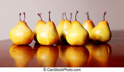 Pears - Several yellow pears on a wooden surface