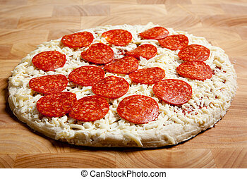 Frozen pepperoni pizza on a cutting board