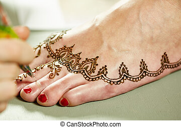 Mehendi. Master applying henna on model's leg, close-up