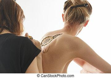 Art of mehendi Master works on naked model, isolated over...