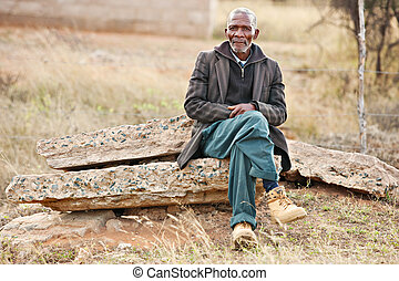 African man resting - senior African man sitting on some...