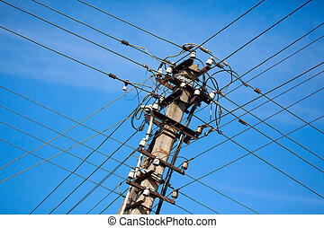 Old electric powerlines against a blue sky