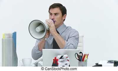 Businessman shouting through a megaphone in office -...