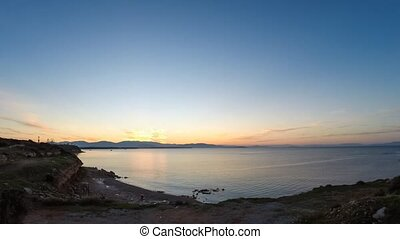 time lapse of calm bay with fishing trawlers on the water and dramatic clouds at sunrise