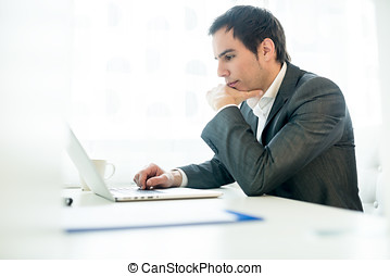 Serious young businessman concentrating on his work as he...