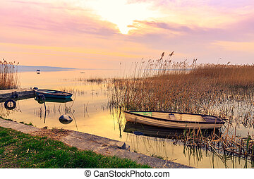 Sunset on the lake Balaton with a boat  in Hungary