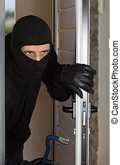 Home burglar - Thief entering a private home to steal