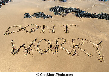 dont worry inscribed on the beach with waves in the...