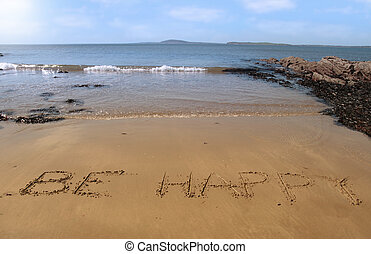 fulfillment - be happy inscribed on the beach with waves in...