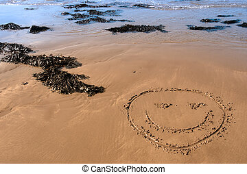 smiley - a smiley face icon inscribed on the beach with...