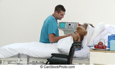 Male doctor playing with a patient and his teddy bear -...