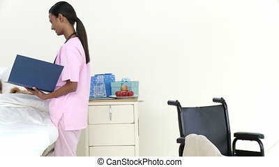 Panorama of Afro-American nurse talking to a little patient...