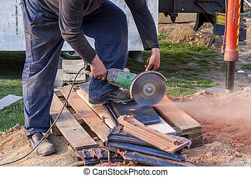 Worker using a hand circular saw to cut a roof-tile