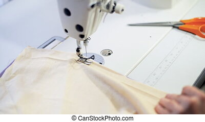 Female hands sewing - Female hands sewing on professional...