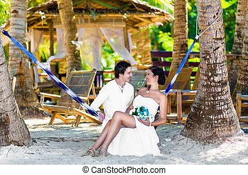 Happy bride and groom having fun in a hammock on a tropical...
