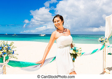 Wedding ceremony on a tropical beach in blue Happy bride...
