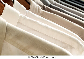 Several shirts on a hanger from white to black color range...