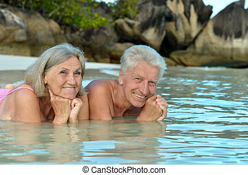 Elderly couple lying on the beach in the water