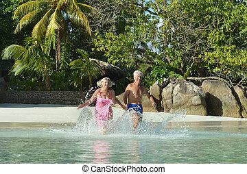 Elderly couple running on the beach near the sea