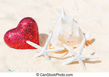Two starfish, big red heart and large shell on a sandy...