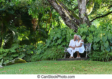 Elderly couple sitting on a bench outdoors - Happy elderly...