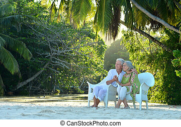 Elderly couple sitting - Beautiful elderly couple sitting on...