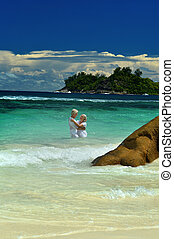 Loving elderly couple bathing in the sea and looking at each...
