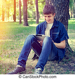 Teenager with Tablet Computer - Toned Photo of Cheerful...