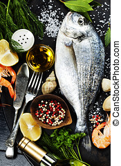 Delicious fresh fish and seafood on dark vintage background...