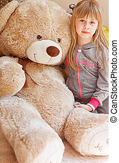 little girl hugging big teddy sitting - little girl hugging...