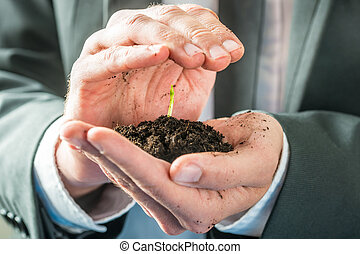 Businessman holding a sprouting seedling in fertile earth...