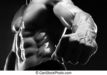 Handsome muscular bodybuilder shows his fist and vein. -...