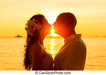 bride and groom kissing on a tropical beach at sunset