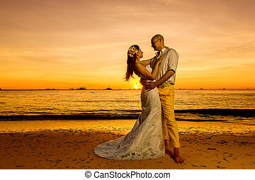 bride and groom on a tropical beach with the sunset in the...