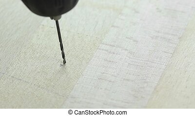 drilling a hole in a wooden board