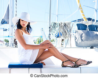 Young woman relaxing on a boat - Young and attractive woman...