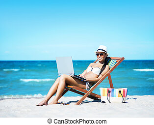 Woman with a laptop on the beach - Young, beautiful, sporty...