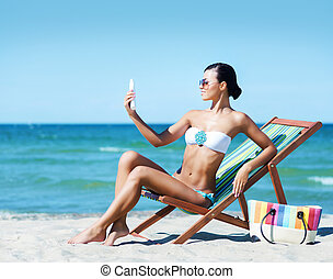 Woman on the beach with suncream - Young, beautiful, sporty...