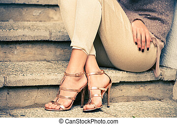 high heels - woman legs in high heel golden sandals sit on...