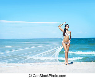 Woman with silk on the beach - Young woman with blowing silk...
