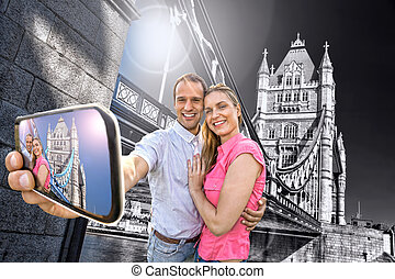 Tourist couple taking selfie against Tower Bridge in London,...