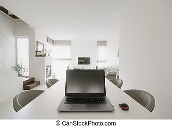 laptop on table in modern dining and living room