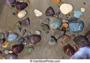 Wet Beach Stones - wet colored stones lying on the sand,...