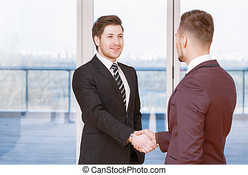Handshake of two partners - Good deal. Two young satisfied...