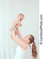 Mother playing with her child and throwing up the baby -...