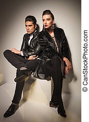 fashion couple sitting together on a white table - Full body...