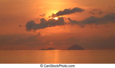 view of sun looking out of clouds above sea islands at dawn...